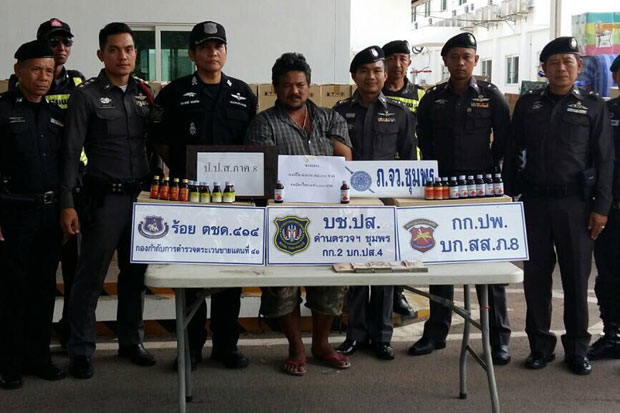 Police show some of the cough suppressants seized from the truck of driver Apinant Kuenoon, centre, at a checkpoint in Chumphon province on Saturday. (Narcotics Suppression Bureau photo)