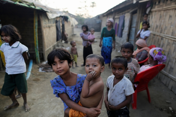 A Rohingya girl carries a baby inside a refugee camp in Sitwe, Rakhine state of Myanmar. (Reuters Photo)