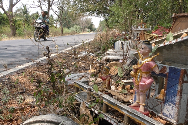 A local motorcyclist keeps to the far side of the road as he passes this discarded old spirit house. (Photos by Chudate Seehawong)