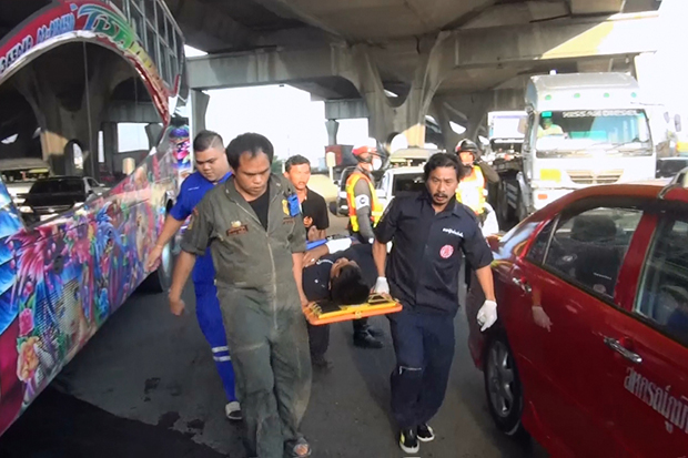 An injured factory worker is carried from the scene of the multiple vehicle   accident on the Bang Na-Trat road in Samut Prakan on Tuesday morning.(Photo by Sutthiwit Chayutworakan)