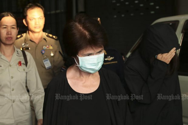 Former Tourism Authority of Thailand (TAT) governor Juthamas Siriwan (in mask) and daughter Jittisopha are escorted to a cell at theCentral Women's Correctional Institution after the Criminal Court session on Wednesday that also denied bail and passed the request to the Appeal Court. (Photo by Patipat Janthong)