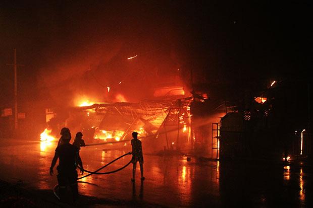Firemen battle the blaze as it destroys three auto parts shops in Pathum Thani early Friday morning. (Photo by Pongpat Wongyala)
