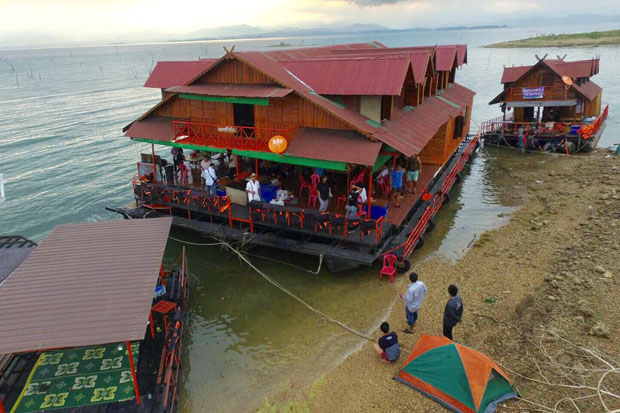 Tourists rest on one of the three rafthouses on an island in the lake of Srinakarin Dam in Kanchanaburi on Sunday morning, waiting for a ferry. (Photo by Piyarach Chongcharoen)