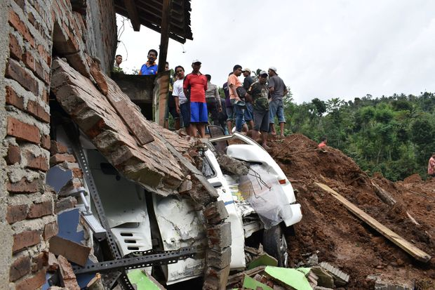 People look at a car damaged and partially buried under a collapsed house after a landslide triggered by heavy rain at Banaran village in Ponorogo, East Java province, on Saturday. (Antara Foto/Siswowidodo via Reuters)
