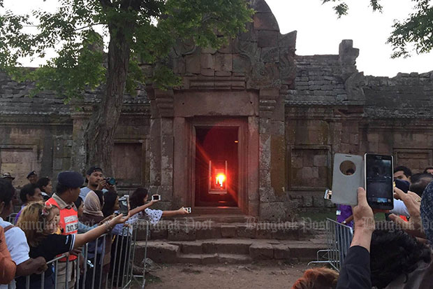 Tourists take photos as the sunrises through all 15 doorways in alignment at the Phanom Rung ruin in Chalerm Phrakiat district of Buri Ram on Monday. (Photo by Surachai Piraksa)
