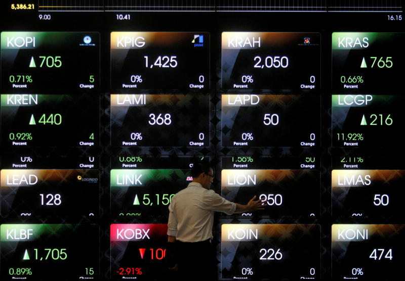 A man examines the electronic stock board at the Indonesia Stock Exchange in Jakarta. The market in Indonesia hit a record high on Monday. (Reuters photo)