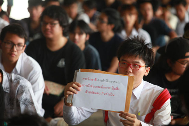 Student activist Netiwit Chotiphatphaisal holds up a sign opposing conscription as he seeks the postponement of his military service this year, at Wat Rath Phothong conscription unit in Muang district of Samut Prakan on Tuesday. (Photo by Somchai Poomlard)