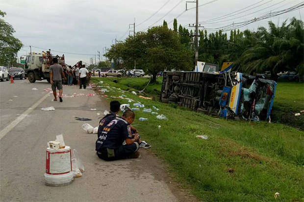 The overturned bus on the side of the road in Surat Thani as emergency crews clear the road at the scene of the crash on Wednesday morning. (Photo by Supapong Chaolan)