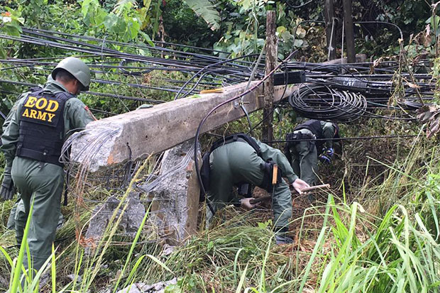 Explosive ordnance disposal officers on Friday morning inspect the scene of an overnight explosion that brought down a power pole in Yala, one of a string of bombings in the three southernmost provinces and part of Songkhla. (Photo by Muhammad Ayub Pathan)