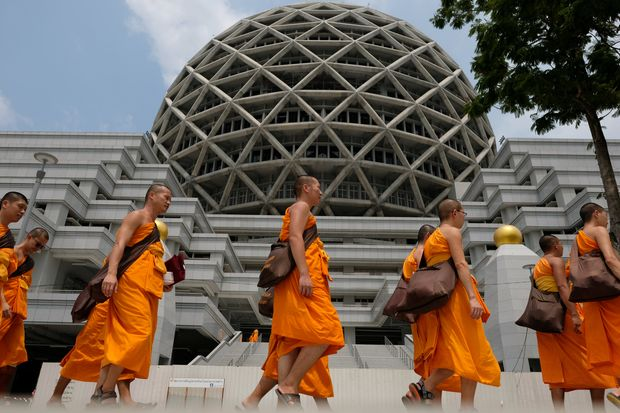Buddhist Monks from Dhammakaya temple walk past a building inside Wat Dhammakaya in Pathum Thani province on March 9, 2017. (Reuters photo)