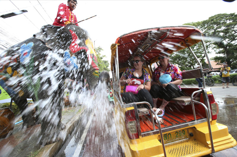 With assist from its mahouts, elephants blow water from its trunk to tourists on motor-tricycle or Tuk Tuk in Ayutthaya on Tuesday. (AP photo)