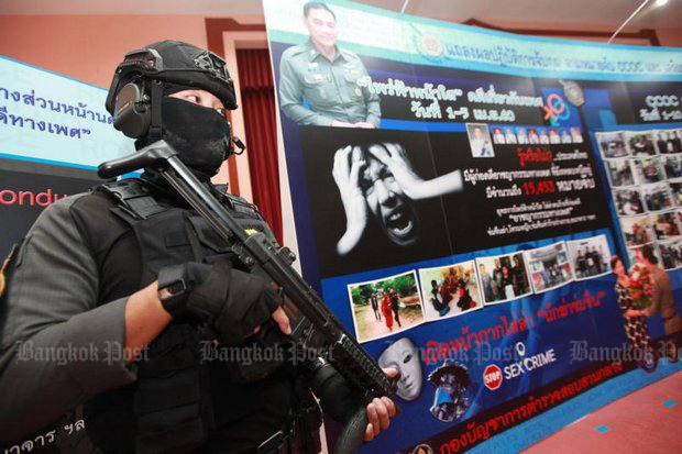 A police officer stands in front of a backdrop banner announcing the Central Investigation Bureau operation to capture most-wanted suspects on sex-related charges. (Photo by Wichan Charoenkiatpakul)