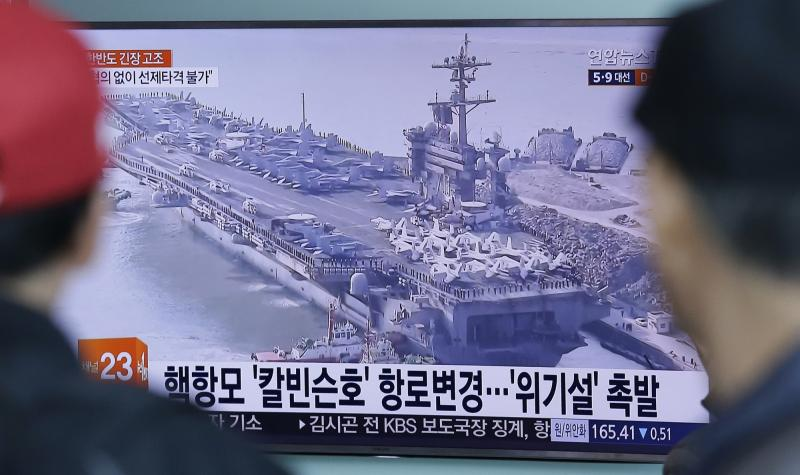 People watch a TV news programme showing a file image of the USS Carl Vinson aircraft carrier at Seoul Railway Station on Wednesday. Tensions in the Korean Peninsula kept a lid on stock gains. (AP photo)