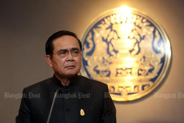 Prime Minister Prayut Chan-o-cha discusses issues with reporters including the missing memorial plaque at Government House in Bangkok on Tuesday. (Photo by Pattarachai Preechapanich)