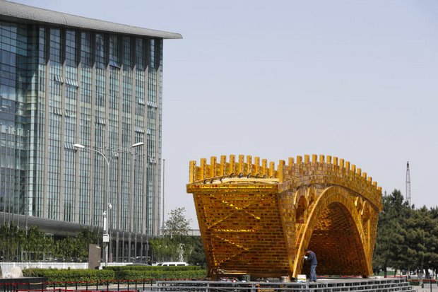 A worker puts the finishing touch on a 'Golden Bridge of Silk Road' structure outside the National Convention Centre in Beijing, where the New Silk Road summit is to be held on May 14-15. (AP photo)
