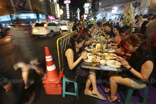 Tourists enjoy a meal close to traffic on Yaowarat Road, Bangkok. (Photo by Patipat Janthong)
