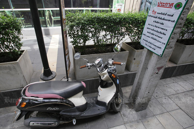 A motorcycle is parked next to an announcement banning the parking on the pavement in Ratchathewi district in Bangkok. (Bangkok Post file photo)