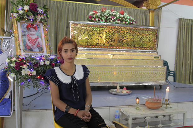 Chiranut Trairat, grieving mother of the murdered 11-month-old girl, sits in front of her daughter's coffin at Wat Si Sunthon in Phuket on Wednesday. (AP photo)