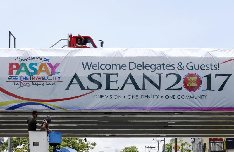 A Filipino in a truck waves as workers install a banner for the Association of South East Asian Nations Summit along a road in Pasay, south of Manila, on Wednesday. (EPA photo)