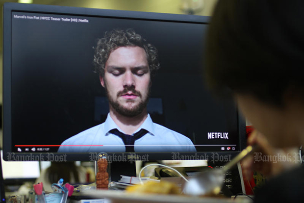 A woman watches a Netflix trailer for Marvel's 'Iron Fist' series on a computer screen. Video-on-demand is emerging as a new choice for consumers in Thailand. (Bangkok Post file photo)