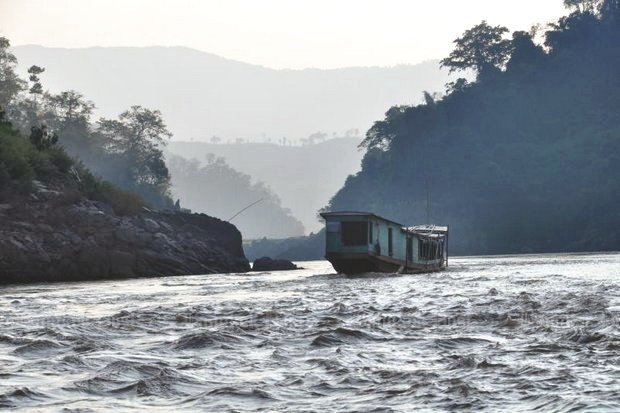 A 'slow boat' sails the Mekong River near the Pak Beng dam site, down-river from Chiang Kong. (File photo by Pianporn Detes)