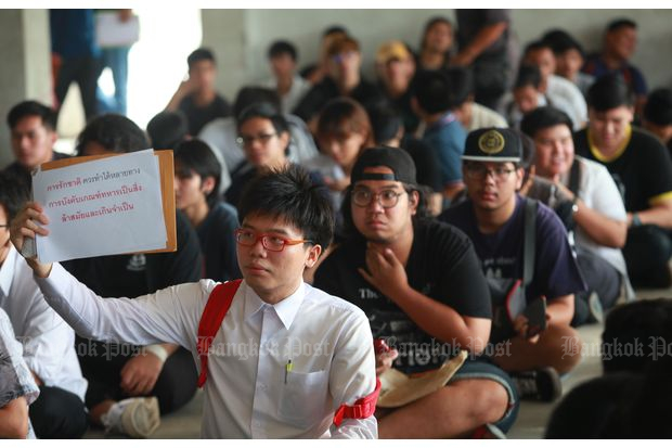 Student activist Netiwit Chotiphatphaisal holds a sign denouncing mandatory conscription as 'obsolete and unnecessary' at a conscription unit at Wat Rat Phothong in Samut Prakan where he went to seek student deferment of his military service on April 4, 2017. (Photo by Somchai Poomlard)