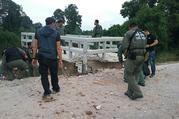 Bomb disposal police inspect a sluice gate on a road along the Sungai Kolok River in Narathiwat following an explosion that injured one member of a five-man patrol team on Friday afternoon. (Photo by Waedao Harai)