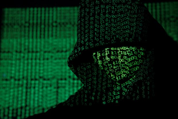 A projection of cyber code on a hooded man is pictured in this illustration picture taken on May 13, 2017. (Reuters photo)