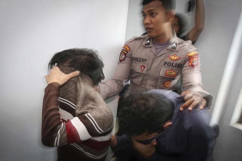 Police officer escorts two men accused of having gay sex into a holding cell to wait for the start of their trial at Shariah court in Banda Aceh, Indonesia, on Wednesday. (AP photo)