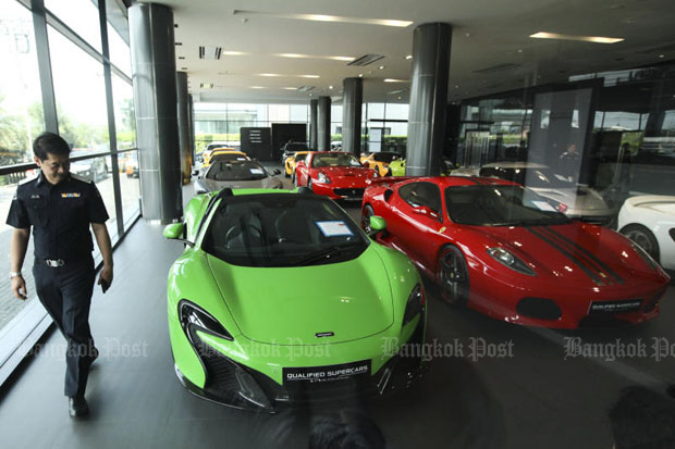 A DSI official inspects supercars in the showroom of Niche Cars Group near the Bangkok-Chon Buri motorway in Suan Luang district, Bangkok, on Thursday. (Photo by Patipat Janthong)
