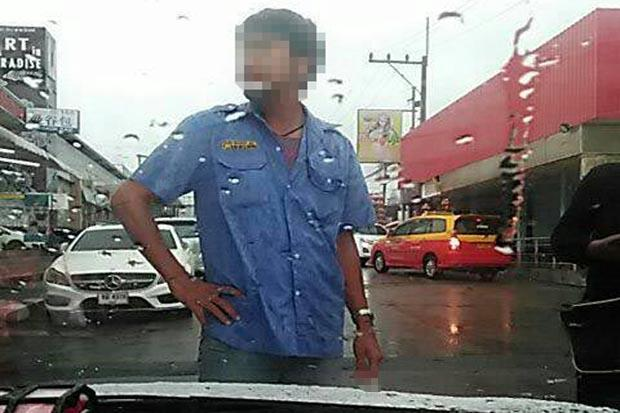 The picture captured from a video by Uber driver Surasak Khukham shows a Pattaya taxi driver standing in front of his vehicle, preventing him leaving.