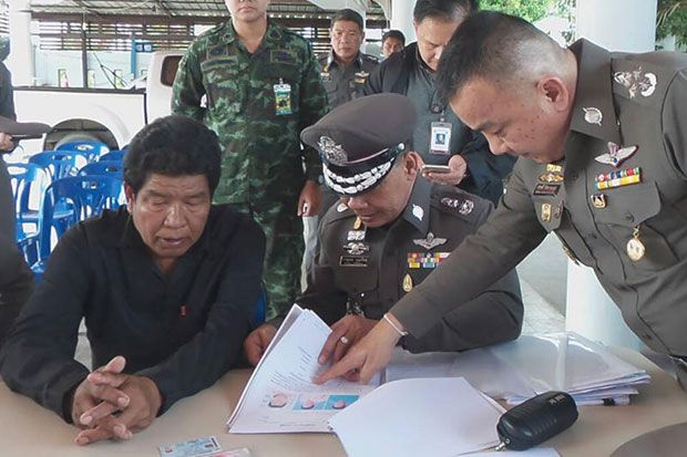 Deputy national police chief Srivara Ransibrhmanakul (right) talks to Chuchart Pea-green (seated left), a tambon administration organisation member of Ban Mai, at a house of the kamnan in Bang Yai district, Nonthaburi, on Friday. (National Police Office photo)