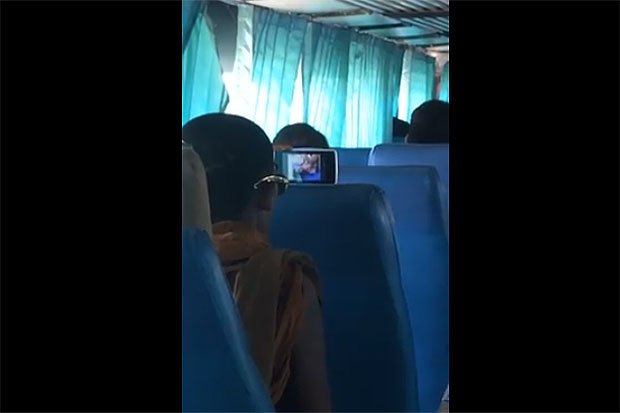 A monk is filmed watching a porn movie on his mobile phone on a bus in Loei province on Saturday. (Photo from a video clip on Wittawat Wonghajuk's Facebook account)