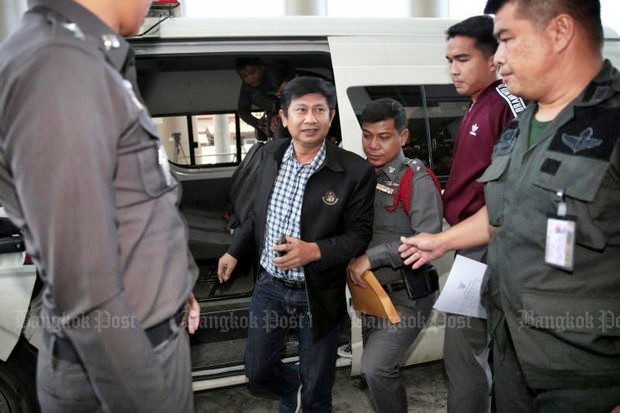 Wasu Phan-ngeon, chairman of Ban Mai tambon administration organisation in Nonthaburi, is escorted to court on charges linked to the Mae Hong Son teen sex scandal. He was charged and freed on bail. (Photo by Chanat Katanyu)