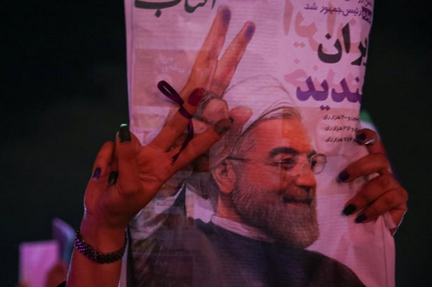 A supporter of Iranian president Hassan Rouhani holds his poster in Tehran as she celebrates his victory in the presidential election in Iran last Saturday. (TIMA via Reuters)