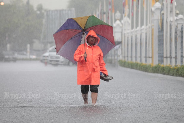 A pedestrian carries his shoes on a flooded path near Government House in Bangkok on Tuesday. (Photo by Chanat Katanyu)