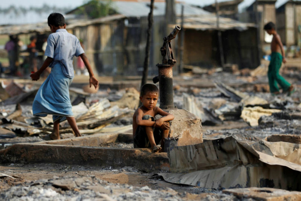 A boy sits in a burnt area after fire destroyed shelters at a camp for internally displaced Rohingya Muslims in the western Rakhine State near Sittwe, Myanmar May 3, 2016. (Reuters photo)