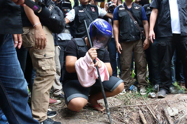 Wasin Namprom, 22, wearing the helmet, shows police how he dug a hole to bury the  murdered karaoke bar woman, in Khao Suan Kwang district of Khon Kaen on Wednesday. (Photo and video by Jakkraphan Nathanri)