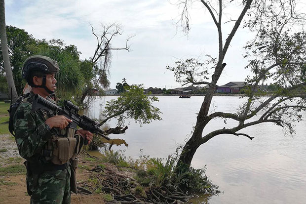 A soldier stands guard on the bank of the Kolok River in Narathiwat province as the army reinforces personnel on the border with Malaysia. (Fourth Army Region photo)