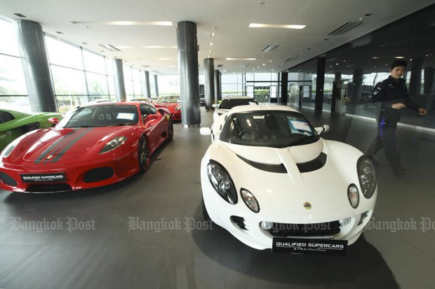 An official walks around a showroom during last month's inspection of luxury cars impounded for alleged evasion of tax and illegal imports. The Customs Department is set to provide information to investigators about the first batch of seized vehicles. (Photo by Patipat Janthong)
