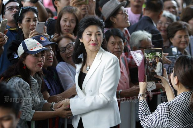 Supporters greet former prime minister Yingluck Shinawatra as she appears at the Supreme Court in Bangkok on Friday. (Photo by Tawatchai Kemgumnerd)