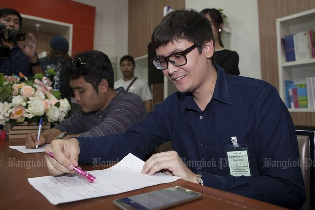 Rangsiman Rome, a Thammasat University activist opposed to the military government, writes his answers to the prime minister's four questions at Government House on Friday. (Photo by Pawat Laupaisarntaksin)