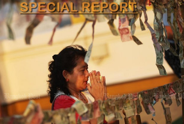 A woman prays at a merit-making event at a temple in Bangkok. A dozen 12 temples in six provinces are under investigation for embezzlement of up to 60 million baht of temple maintenance funds. The scandal involves former and active officials of the National Office of Buddhism. (Photo by Seksan Rojjanametakun)