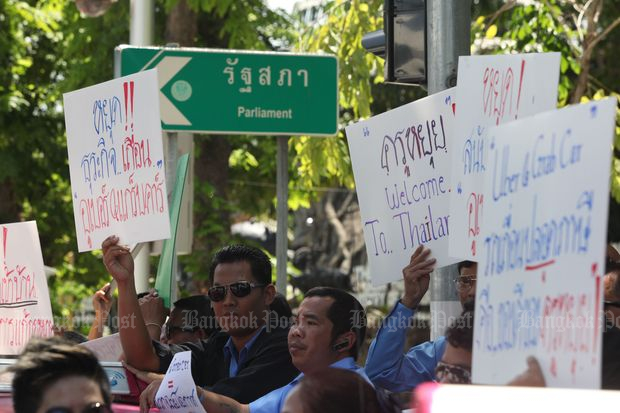 Some 30 taxi drivers protest against ride-sharing service providers Uber and Grab at Parliament on Friday. (Photo by Thiti Wannamontha)