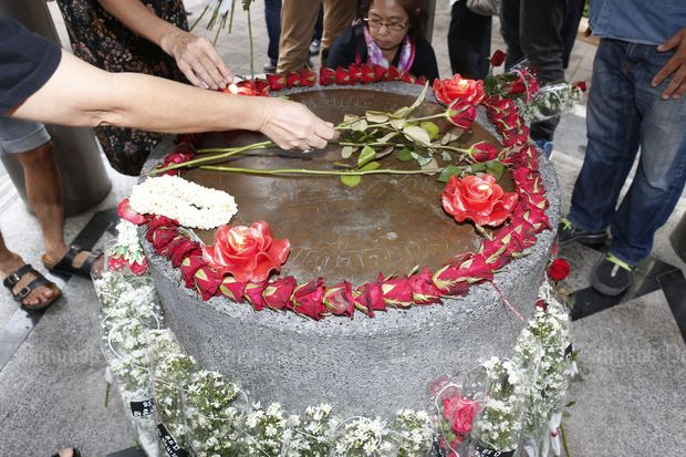 Flowers are placed on the replica of the People's Party plaque in Thammasat University on Saturday to mark the 85th anniversary of the Siam Revolution. (Photo by Pattarapong Chatpattarasill)