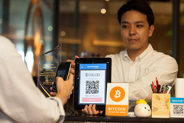 Mr Tewit shows a customer how to pay for their meal with bitcoin. (Photos by Pawat Laopaisarntaksin)