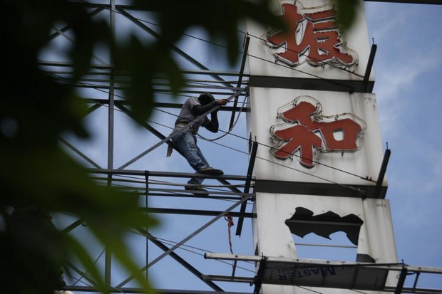 A worker clambers up a scaffold to fix a sign on a Yaowaraj Road gold shop on Monday. New rules of hiring foreign workers will impact such jobs. (AP photo)