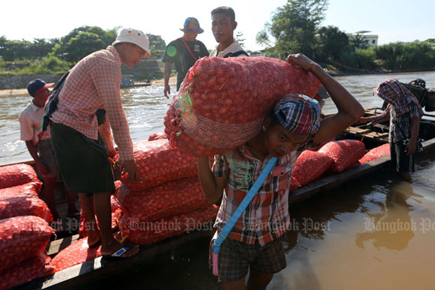 Men unload farm goods at the border town of Mae Sot in Tak province. (Bangkok Post file photo)