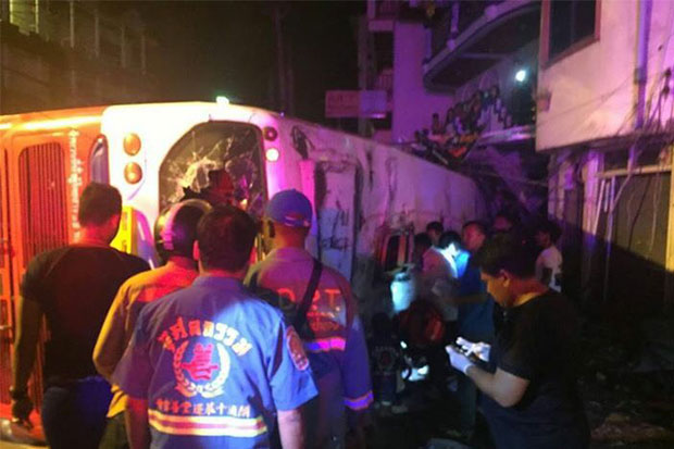 Rescue workers at the scene of the bus crash in front of Wat Suwankhiriwong on Phra Baramee Road in Patong, Kathu district of Phuket, on Monday night. Two Chinese tourists were killed, one a young boy, and 24 other injured.(Photo by Achataya Chuenniran)