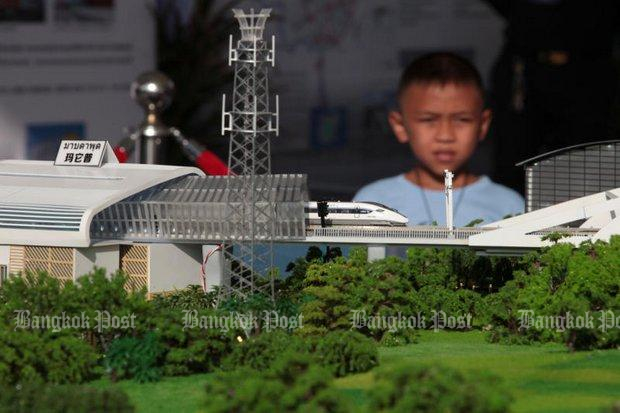 A youngster checks out a model of the proposed Bangkok-Nakhon Ratchasima railway, with the final design and construction details to be settled soon. (File photo)